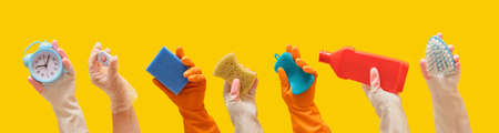 general cleaning and cleaning service concept, hands in rubber gloves hold cleaning tools yellow background banner