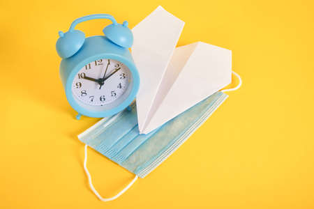 alarm clock, paper plane and medical face protective mask on yellow background copy space lockdown and tourism concept Banco de Imagens
