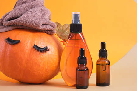 mock up set of cosmetic containers with pipettes from amber glass and pumpkin with towel and false eyelashes on orange background, natural skin care in autumn concept