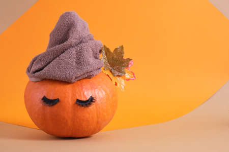 orange pumpkin with towel and false eyelashes on orange background copy space autumn skin care concept copy space