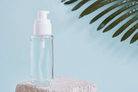 two mock up blank glass bottle with a white cap on a concrete podium on a light blue background, cosmetic bottles, a bottle with gel and perfume palm leaf on background Banco de Imagens