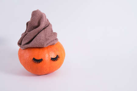 orange pumpkin with towel and false eyelashes on gray background copy space