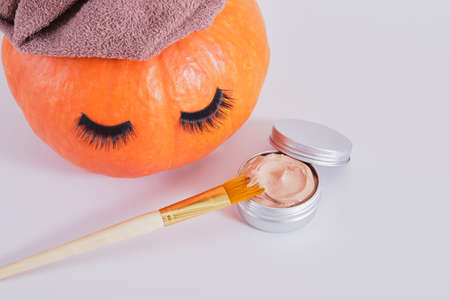 brush, aluminum jar with cosmetic clay face mask and orange pumpkin with towel and false eyelashes on gray background, natural skin care in autumn concept Banco de Imagens