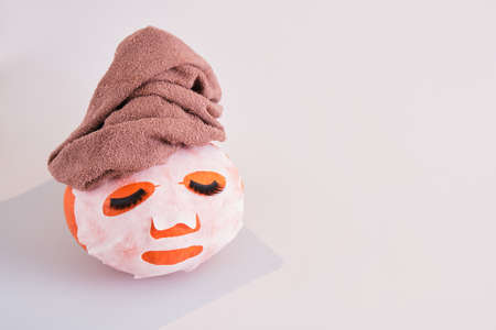 pumpkin with towel, fabric mask and false eyelashes on gray background, skin and body care in autumn concept, spa salon concept Banco de Imagens
