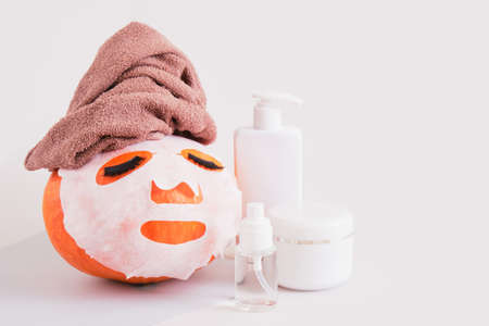 pumpkin with towel, cloth mask and false eyelashes on gray background, bottle, jar and spray with cosmetics without label mock up Banco de Imagens