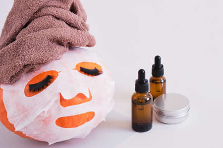 pumpkin with towel, cloth mask and false eyelashes on gray background, amber glass bottles with pipettes and aluminum jar with cosmetic product without label, skin care concept Banco de Imagens