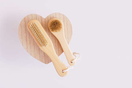 wooden brushes for massage and body skin care on wooden heart-shaped stand, gray background copy space
