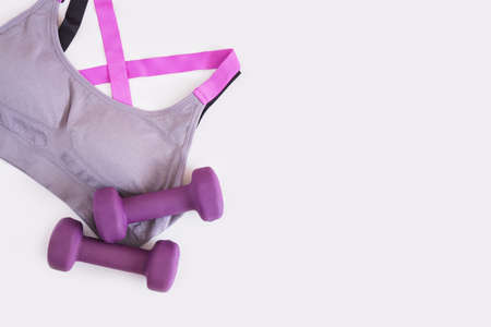 sports bra and two dumbbells on a gray background copy space Banco de Imagens