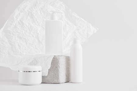set of packaging for cosmetics on a concrete podium against a background of crumpled white paper, a blank for a can and bottles with creams or lotions, mock up cosmetics product concept