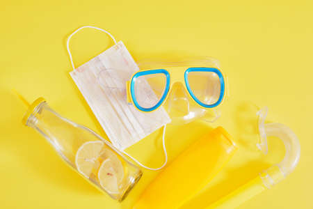 diving mask, protective medical mask, sunblock and lemonade bottle on yellow background, beach vacation concept in lockdown