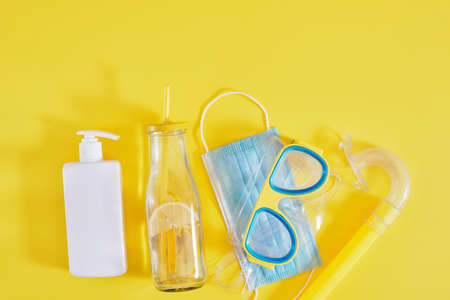 diving mask, protective medical mask, sun cream and a bottle of lemonade on a yellow background, tourism and recreation during the coronavirus pandemic