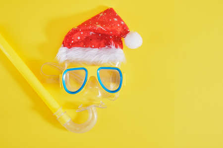 diving set, santa claus hat, sun cream and a bottle of lemonade on a yellow background, Christmas holidays on the beach in a warm country