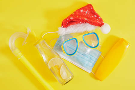 diving set, protective medical mask, santa claus hat, sun cream and a bottle of lemonade on a yellow background, Christmas holidays in a warm country during a pandemic