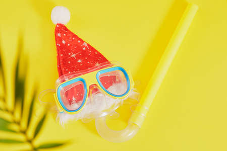 scuba diving set, santa claus hat and palm leaf on yellow background, Christmas holidays on the beach in a warm country