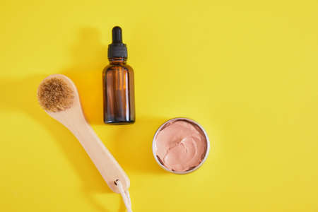 face care set, cosmetic clay, wooden massage brush and amber dropper bottle, yellow background top view copy space Banco de Imagens