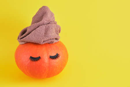 pumpkin with towel and false eyelashes on yellow background, skin and body care in autumn concept, spa salon copy space