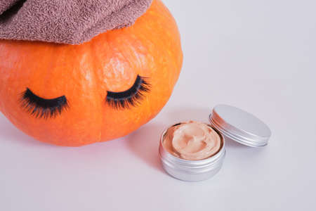 aluminum jar with cosmetic clay face mask and orange pumpkin with towel and false eyelashes on gray background, natural skin care in autumn concept Banco de Imagens