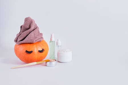 mock up set of cosmetic containers and pumpkin with towel and false eyelashes on gray background, natural skin care in autumn concept, gel, clay and bath salt
