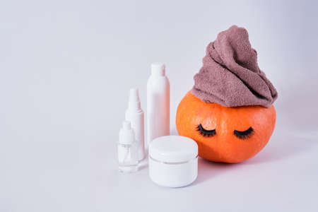 mock up set of cosmetic containers and pumpkin with towel and false eyelashes on gray background, natural skin care in autumn concept