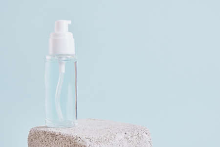 two mock up blank glass bottle with a white cap on a concrete podium on a light blue background, cosmetic bottles, a bottle with gel and perfume