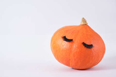 pumpkin with false eyelashes on gray background copy space autumn, autumn season concept Banco de Imagens