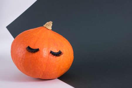 pumpkin with false eyelashes on a dark green background autumn, autumn season concept