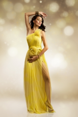 wind dress: beautiful sexy young woman wearing yellow evening dress