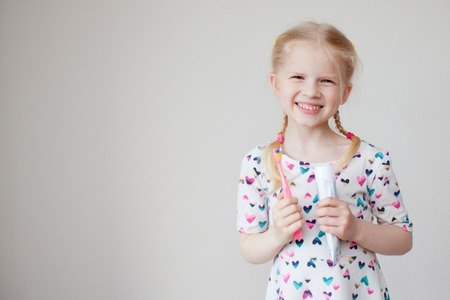 Little beautiful blonde girl smiling at camera. With toothpaste and toothbrush in hand.Health care, dental hygiene