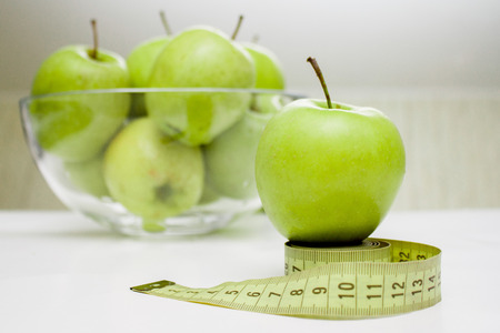 Diet, healthy eating, food and weigh loss concept. Measuring tape and green apple