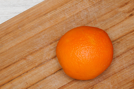 Orange ripe fruit  on wooden board in kitchen. Fresh citrus orange on cutting board for salad or juicing. Healthy eating, cooking, diet and summer concept.