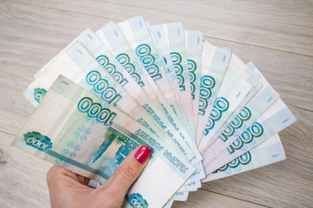 business, finance, saving, banking and people concept - close up of woman hands with bundle of money Russian Banknotes thousand rubles on wooden table Stock Photo