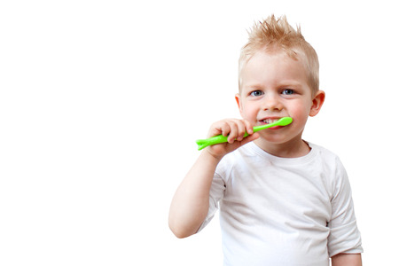 Happy child kid boy brushing teeth on white background. Health care, dental hygiene, people and beauty concept. Mockup, free space. Stock fotó