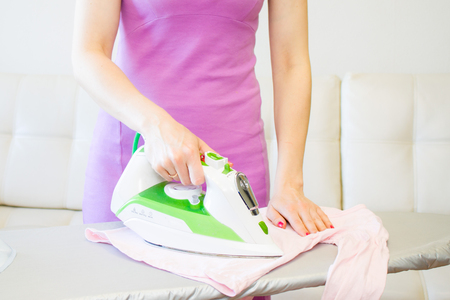 Woman Ironing kids pink Clothes Using Iron On Ironing Board After Laundry At Home