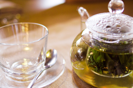 Beverages, good morning and breakfast concept - empty tea cup and teapot with green tea on the table 写真素材