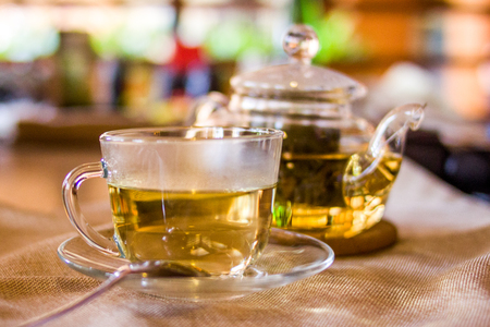 Beverages, good morning and breakfast concept - Cup of white green tea and teapot on the table