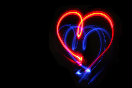 Coeur dessiné avec des lumières rouges et bleues. Fond de nuit noire. Freezelight. Concept d'amour, romantique et festif