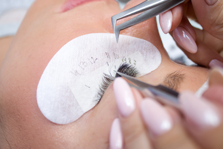 Beauty and fashion concept - Eyelash Extension Procedure. Woman Eye with Long false Eyelashes. Master of tweezers is working.