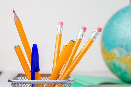 Back to school and education concept - school office supplies pencils, pens in stand, paper, notebook and globe on boke background. for educational new academic year begin or study term start.