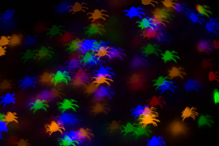 defocused bokeh multicolor lights in shape of spiders for halloween background - holidays, decoration and party concept