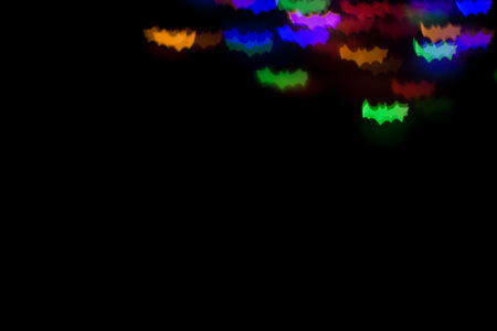 defocused bokeh multicolor lights in shape of bats for halloween background. copy space - holidays, decoration and party concept