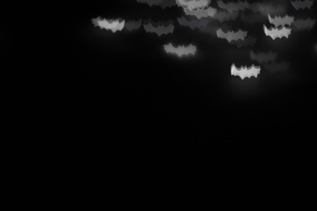 defocused white bats silhouette ghosts on black for halloween background. copy space - holidays, decoration and party concept Stock Photo
