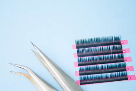 Beauty and fashion concept - tools for Eyelash Extension Procedure. Two tweezers with false lashes on blue background. copyspace mockup