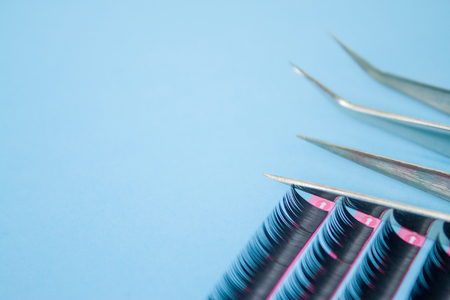Beauty and fashion concept - tools for Eyelash Extension Procedure. Two tweezers with artificial black lashes on blue background. copyspace mockup