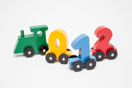 wooden numbers 0,1,2 letters train alphabet . Bright colors of red yellow green on a white background. Early childhood education, learning to count, preschool and kids game concept. Фото со стока