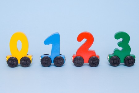 wooden numbers 0,1,2,3 letters train cars alphabet . Bright colors of red yellow green on a white background. Early mathematic education, learning to count, preschool and kids game concept. Stock Photo