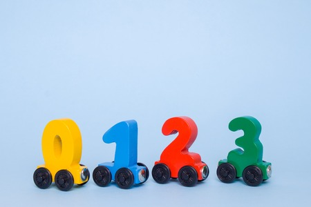 wooden numbers 0,1,2,3 letters train cars alphabet . Bright colors of red yellow green on a white background. Early mathematic education, learning to count, preschool and kids game concept. copyspace