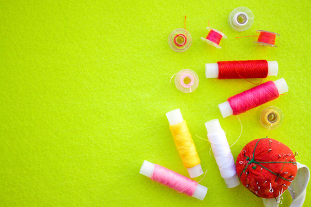 Multicolored thread coils red pink yellow white and measuring tape on green background. Sewing supplies and accessories for needlework, stitching, embroidery. space for text