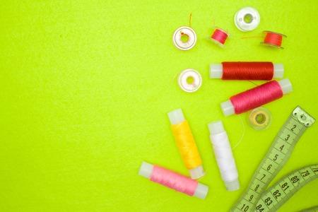 Mehrfarbige Gewindespulen rot rosa gelb weiß und Maßband auf grünem Hintergrund. Nähzubehör und Zubehör für Handarbeiten, Nähen, Sticken. Platz für Text Standard-Bild