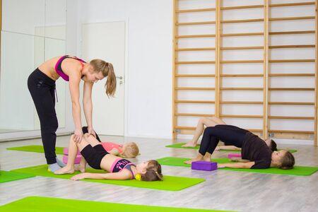 istruttore di fitness spiega come eseguire correttamente l'esercizio. Urdhva Dhanurasana e posa del ponte - ginnastica, stretching, yoga e concetto di sport per bambini.