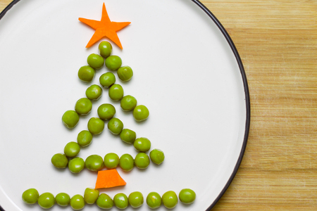 Funny edible Christmas tree made from peas and carrots, Breakfast idea for kids. New Year food background top view . holiday, celebration, food art concept